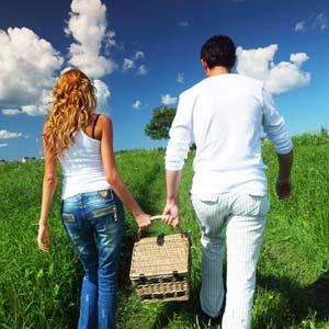 Coppia cammina con cestino da piknik lungo un sentiero in un prato verde