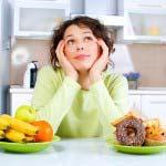 Ragazza indecisa se mangiare frutta o dolci
